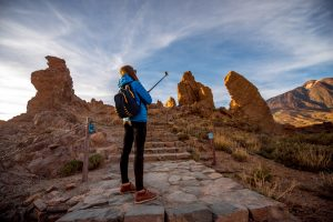 Young female traveler making selfie with small action camera on a stick on the beautiful rocky background in Teide park on Tenerife island